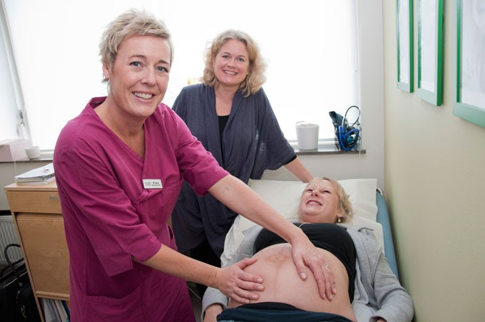 Nurse examining a pregnant woman´s belly
